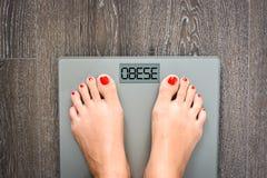Hulp om kilogram te verliezen die met vrouwenvoeten op een gewichtsschaal stappen Stock Foto's