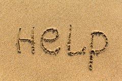 HULP - op de textuur van overzees zand manueel wordt geschreven dat nave Royalty-vrije Stock Foto