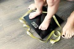 Hulp vet of zwaarlijvig die kind met peuter op gewichtsschaal, door een ouder gecontroleerd stock afbeeldingen