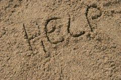 Hulp in zand wordt geschreven dat stock fotografie