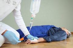 Hulpdienst die een infusie geven aan een patiënt royalty-vrije stock afbeelding