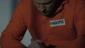 Hulpeloze Kaukasische gevangene in individuele cel die camera, wanhoop bekijken stock videobeelden