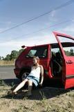 Hulpeloze zwangere vrouwenzitting dichtbij rode auto royalty-vrije stock afbeelding