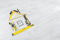 Hulpmiddelen in de vorm van huis over houten vloer Stock Foto's
