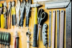 Hulpmiddelen en apparaten die op workshopmuur hangen Heersers, die kniv snijden royalty-vrije stock afbeeldingen