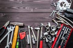 Hulpmiddelen en autovervangstukken op houten werkbank De ruimte van het exemplaar stock afbeeldingen