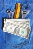 Hulpmiddelen en contant geld in zak Stock Afbeelding