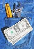 Hulpmiddelen en contant geld in zak Royalty-vrije Stock Afbeelding