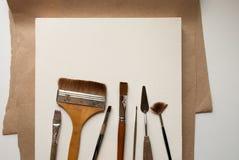 Hulpmiddelen om te schilderen Borstels, paletmessen en wit canvas Royalty-vrije Stock Foto
