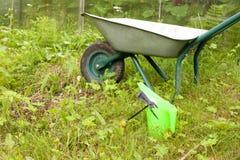 Hulpmiddelen om te tuinieren Hark, gieter en kruiwagen Stock Fotografie