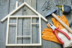Hulpmiddelen op houten raad met huis stock afbeeldingen