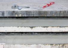 Hulpmiddelen: Troffel twee, het niveau op de stappen en de houten bekisting vulden met concrete mengeling royalty-vrije stock afbeeldingen