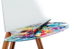 Hulpmiddelen van de kunstenaar Brushes, houten schildersezeldriepoot, kleurrijk palet witte achtergrond, studio, niemand Geïsolee royalty-vrije stock fotografie