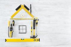 Hulpmiddelen in vorm van huis. Houten achtergrond Stock Fotografie