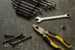 Hulpmiddelreeks buigtang, moersleutels, bouten en noten op abstracte grijze oppervlakte stock afbeelding