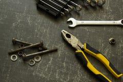 Hulpmiddelreeks buigtang, moersleutels, bouten en noten op abstracte grijze oppervlakte royalty-vrije stock afbeeldingen