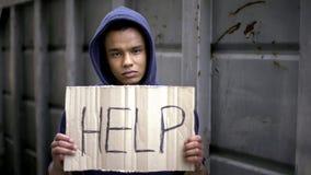 Hulpteken in het bedelen van Afro-Amerikaanse jongenshanden, eindeoorlog, vluchtelingsprobleem stock afbeeldingen