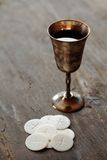 Huly communion. Chalice with wine and communion wafers on wooden background Stock Image