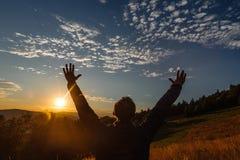 Humain avec des mains se levant en montagnes pendant un lever de soleil Photographie stock