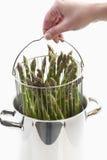 Humain tenant faire cuire le pot avec l'asperge verte photos libres de droits