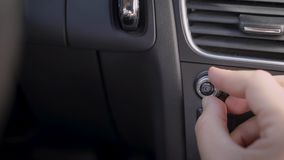Human is adjusting volume of radio inside car, rotating handle on control panel, close-up of hand. And fingers, driver or passenger stock footage