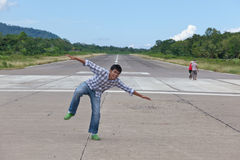 Human airplane taking off. Asian dude mockingly playing a human airplane on the commercial jungle strip on tropical island Camiguin (Philippines) while villagers Stock Photography