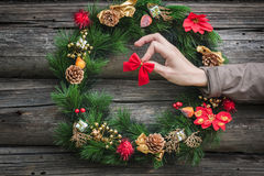 Human arm hanging red bow on rustic log cabin wall with festive winter wreath Stock Images