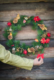 Human arm holding decorative red bow near outdoor Christmas wreath at log cabin wall background Royalty Free Stock Photos