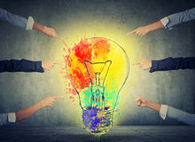 Human arms fingers point at idea colorful light bulb Royalty Free Stock Photo