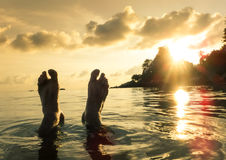 Human barefeet at beach on sunset in Koh Lipe. Naked human barefeet at seaside water during sunset in Koh Lipe - Wanderlust travel concept with wonderful South Stock Photography