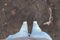 Human Blue Denim Pants and Black Low Top Sneakers Standing on Brown Sand Stock Photo