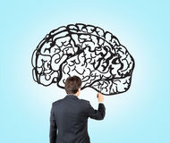 Human brain. Businessman drawing image of brain on blue wall. Back view. Concept of mental work Stock Photos