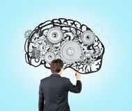 Human brain. Businessman drawing image of brain with gears on blue wall. Back view. Concept of mental work Stock Images