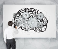 Human brain. Businessman drawing image of brain with gears on white poster. Back view. Grey background. Concept of mental work Stock Photos