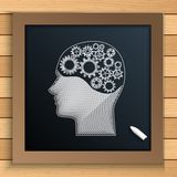 Human brain mechanism with cogs and gears written by chalk on blackboard Stock Photo