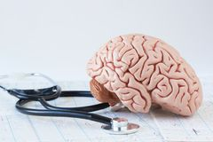 Human brain model and a black stethoscope on background of brain waves