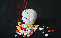 Human brain model with red needles and multi-colored pills - the concept of migraine, headache, neurology. stock photography