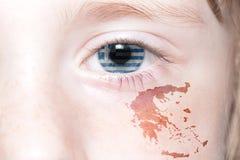 Human& x27; cara de s con la bandera nacional y el mapa de Grecia Fotografía de archivo libre de regalías