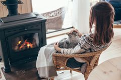 Human with cat relaxing by the fire place. Human with cat relaxing in wicker armchair by the fire place in wooden cabin. Warm and cozy winter holiday concept stock photography