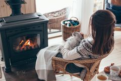 Human with cat relaxing by the fire place. Human with cat relaxing in wicker armchair by the fire place in wooden cabin. Warm and cozy winter holiday concept royalty free stock photos
