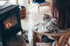 Human with cat relaxing by the fire place. Human with cat relaxing in wicker armchair by the fire place in wooden cabin. Warm and cozy winter holiday concept royalty free stock photo