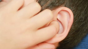 Human child ear close up. earache, otitis. Child touches a sore ear
