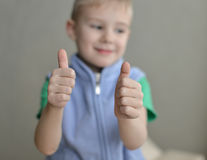 Human child hand gesturing thumb up success sign. On gray background Royalty Free Stock Images