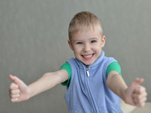 Human child hand gesturing thumb up success sign. On gray background Royalty Free Stock Photo