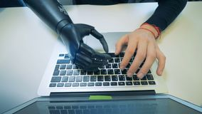 A human cyborg with robotic hand working on a laptop, top view. A worker types on a laptop, using his artificial hand