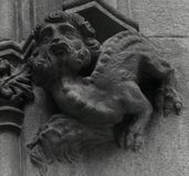 Human dragon holding a head on its claw. Shot in black and white detail on the sculpture on the facade of this historic building representing some characters royalty free stock image