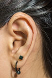 Human ear closeup with metal earring Stock Images