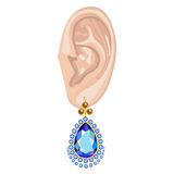 Human ear & hanging earring Royalty Free Stock Image