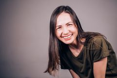 Human emotion. Beautiful brunette woman smiling and laughing at camera. Charming laugh royalty free stock photography