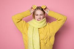 Human emotions. Blonde beautiful european girl in yellow sweater and scarf showing funny face, holding two sliced citrus. Lemons on her head, isolated over pink royalty free stock image